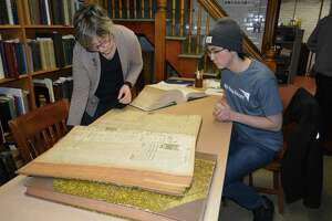 "Torrington Historical Society Curator Gail Kruppa helps local student Lucas Rodriguez, 16, research his project as part of the ""Digging into History,"" program by the Connecticut State Library."
