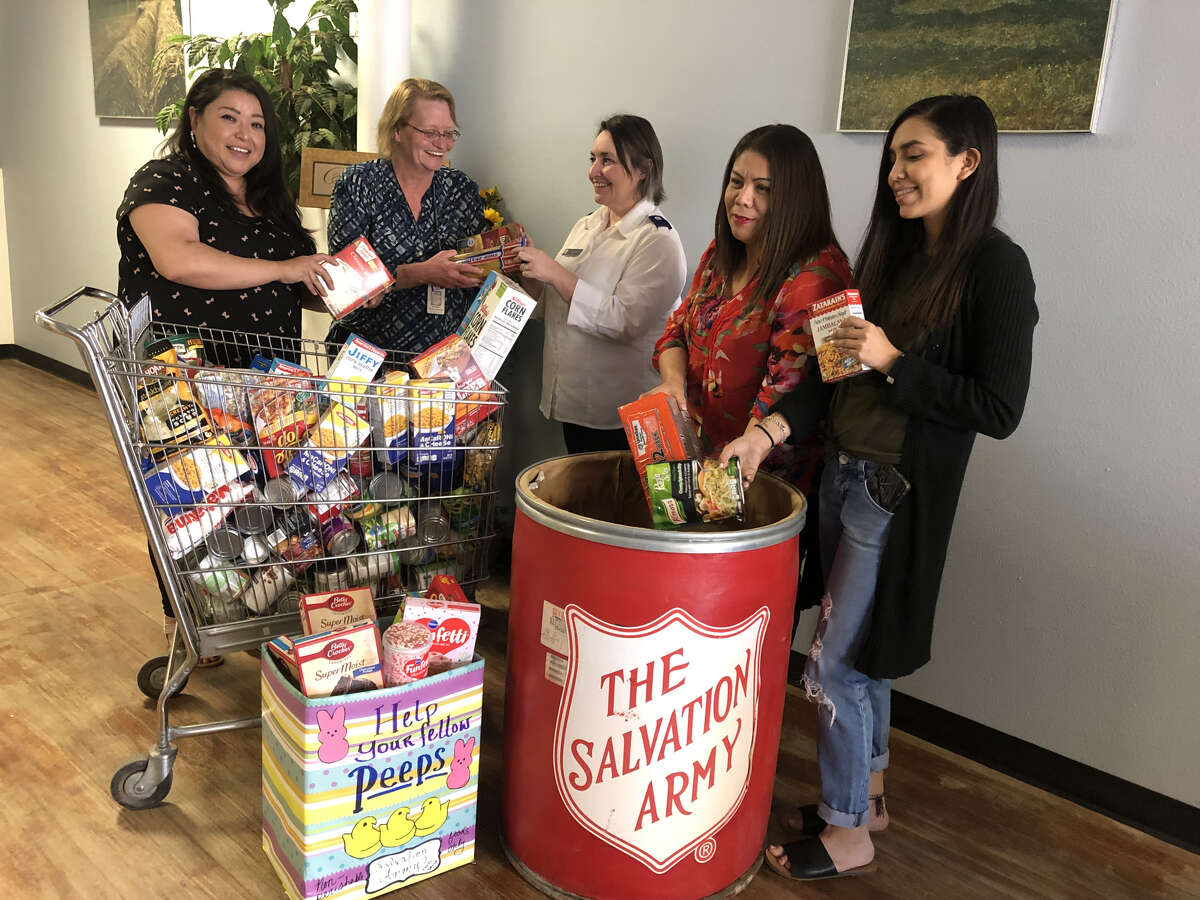 (left to right) CPC employees Noemi Barrientos, Rita Settle, Salvation Army Director Michelle Rutherford, CPC employees Lorena Gonzales and Jessica Pena are filling the RED BARREL with the food donated by CPC employees.