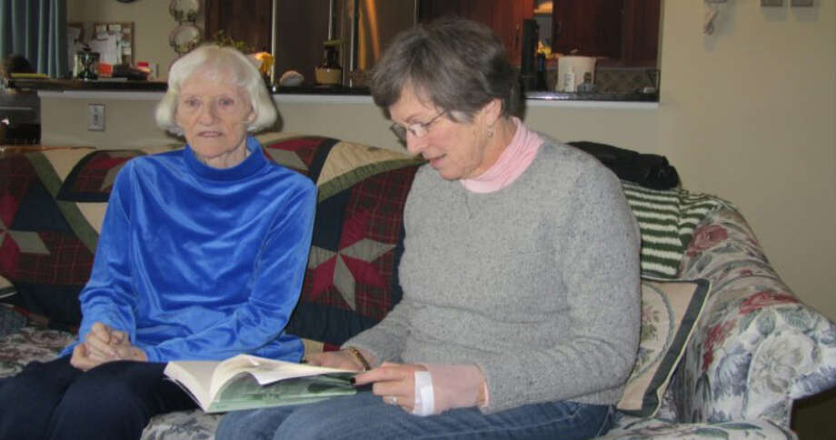 A Mercy Care for the Adirondacks Friendship Volunteer reads to an elder who is visually impaired. Photo: Provided