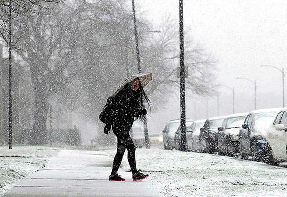 A woman walks on the sidewalk Sunday in Chicago. Photo: Nam Y. Huh   AP