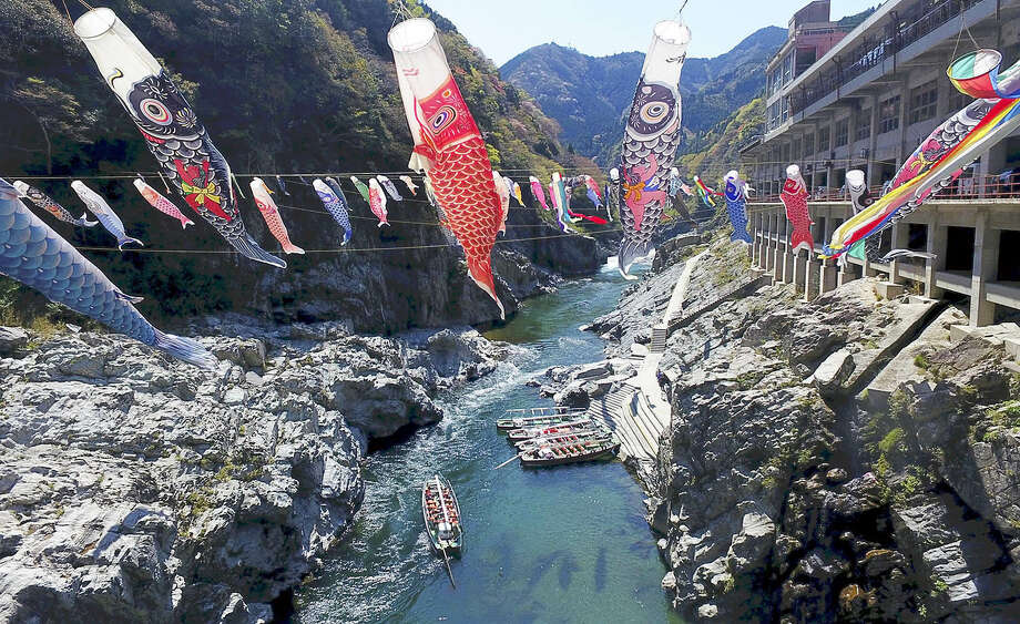 "STANDALONE PHOTO: In Japan's Oboke Gorge, a scenic area in Tokushima Prefecture sandwiched between sheer cliffs, about 180 colorful koinobori carp streamers in red, blue and many other colors ""swim"" in the spring breeze. Carp streamers are flown every spring to celebrate Tango no Sekku, Japan's traditional boys' festival. Photo: Japan News-Yomiuri / Japan News-Yomiuri"