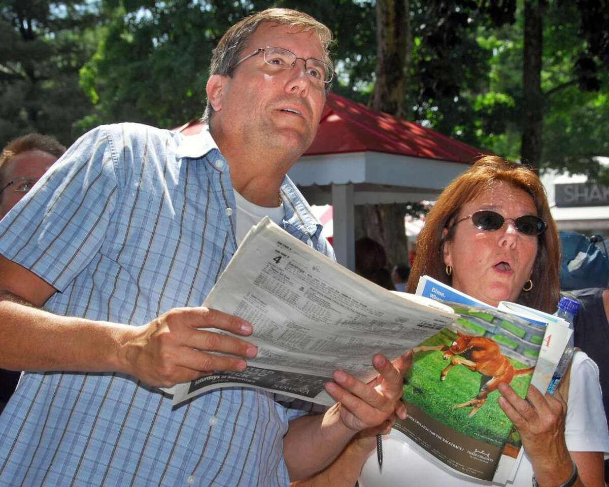 Phil and Mary Lou Collura of Center City, N.J., cheer their picks at a television monitor inside Saratoga Race Course in Saratoga Springs on Saturday, July 24,2010. The Colluras own trotters and race all over the eastern states but this is their first time at Saratoga Race Course. (John Carl D'Annibale / Times Union)