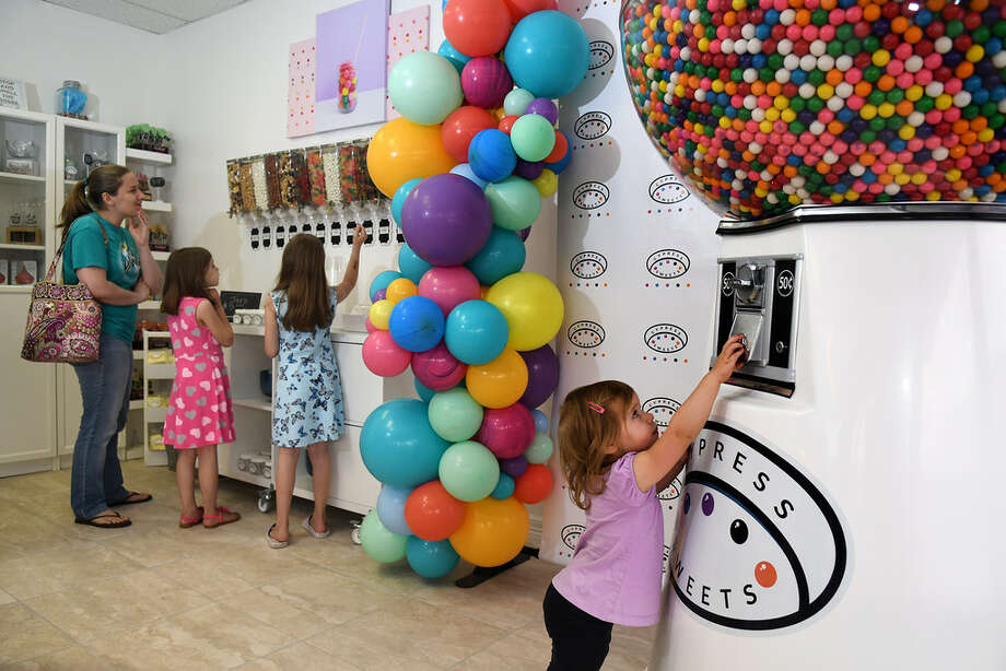 Elliana Hubbard, 2, right, checks out the gumball machine while her mom Kim, from left, of Tomball, and sisters Addison, 7, and Olivia, 9, browse the other goodies at Cypress Sweets during the store's grand opening in Cypress on April 13, 2019. Photo: Jerry Baker, Contributor