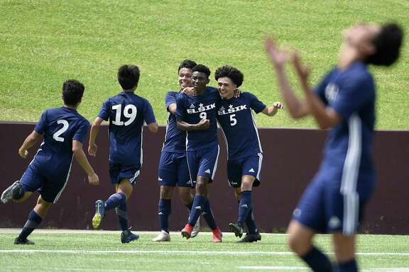 Elsik midfielder Dandord Ndabah (9) celebrates his goal with Andrei Aguirre (5) and teammates during the second half of a 6A region 3 final high school soccer match against Spring Woods, Saturday, in Deer Park.