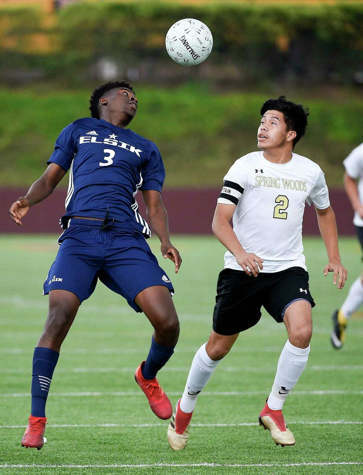 Elsik defender Samuel Nseng (3) heads the ball as Spring Woods defender Walter Constanza defends during the first half of a 6A region 3 final high school soccer match, Saturday, April 13, 2019, in Deer Park.