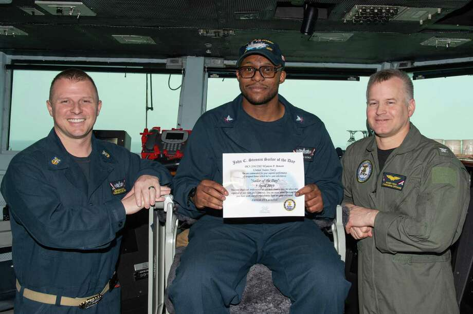U.S. Navy Damage Controlman 3rd Class Wynton Bowen of Houston poses for a photograph as the Sailor of the Day with Capt. Randy Peck, right, commanding officer of the aircraft carrier USS John C. Stennis (CVN 74), and Command Master Chief Benjamin Rushing in the Arabian Gulf, April 5. The John C. Stennis Carrier Strike Group is deployed to the U.S. 5th Fleet area of operations in support of naval operations to ensure maritime stability and security in the Central Region, connecting the Mediterranean and the Pacific through the western Indian Ocean and three strategic choke points. Photo: Mass Communication Specialist Seaman Jeffery L. Southerland, USS John C. Stennis (CVN 74) / U.S. Navy Photo / Digital