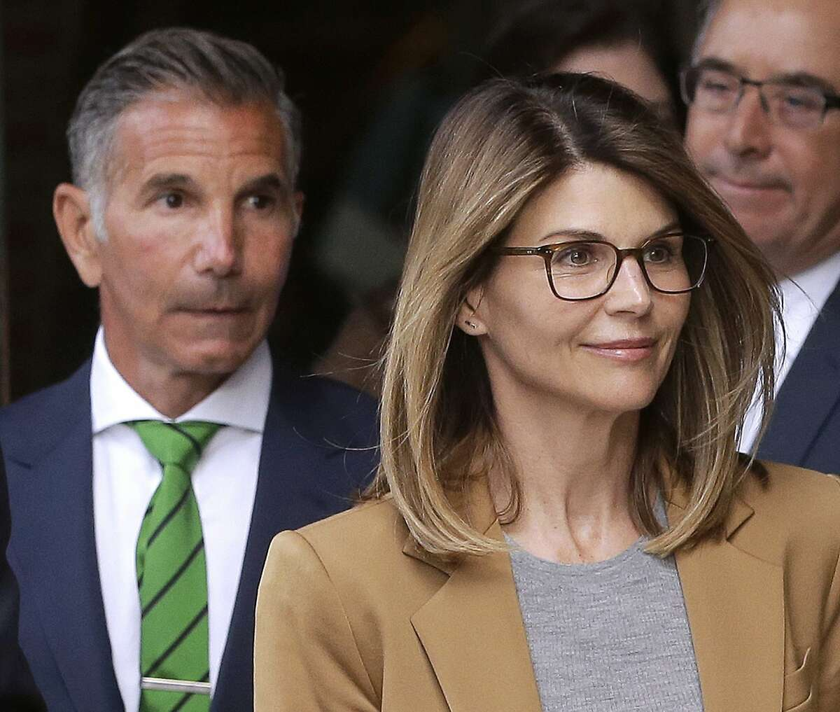 FILE - In this April 3, 2019 file photo, actress Lori Loughlin, front, and husband, clothing designer Mossimo Giannulli, left, depart federal court in Boston after facing charges in a nationwide college admissions bribery scandal.
