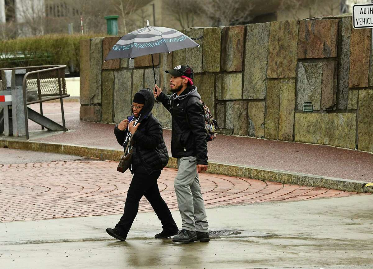 A man holds an umbrella over a woman as they walk in the rain up Madison Ave. on Friday, April 12, 2019 in Albany, N.Y. (Lori Van Buren/Times Union)