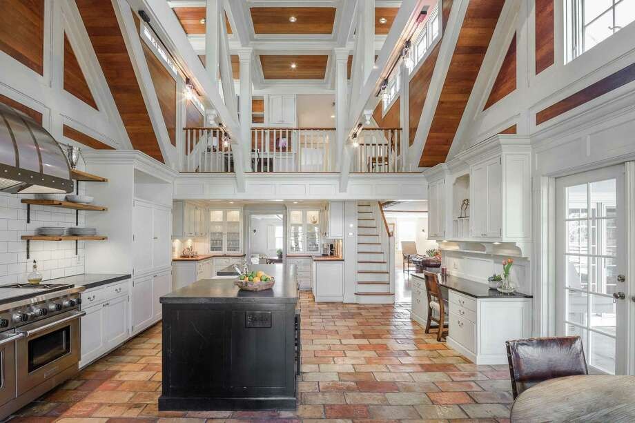 The kitchen features a double-height cathedral ceiling, open shelving, new appliances, a new island and French roofing tile floors with radiant heating. Photo: William Raveis Real Estate / ONLINE_CHECK