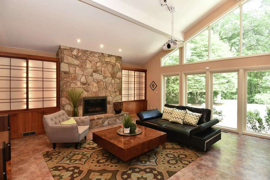 The first floor family/media room features floor-to-ceiling custom cherry cabinets with back-lit Shoji screens, dramatic stonework framing the fireplace and a wall of windows. Photo: William Raveis Real Estate / ONLINE_CHECK