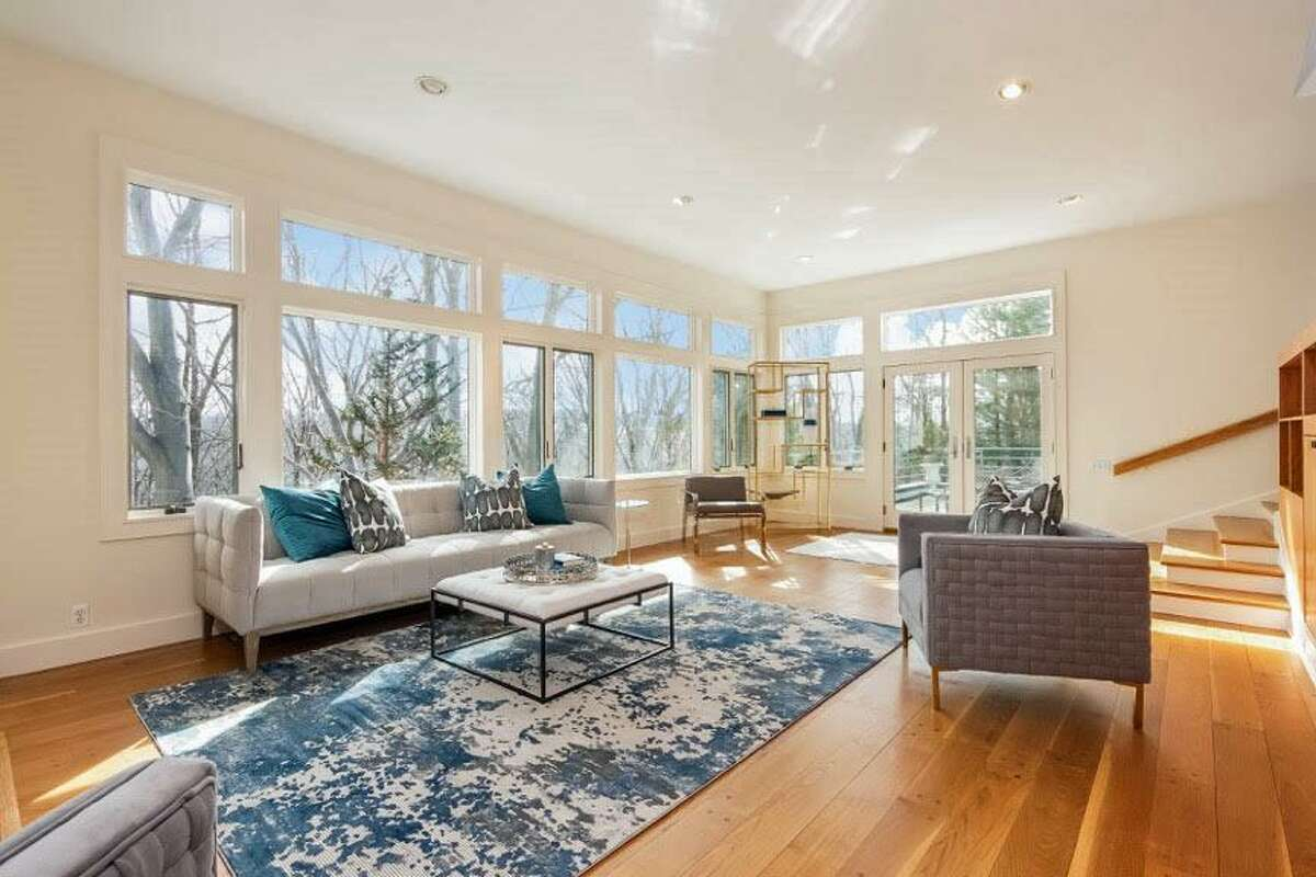 The living room has a fireplace and French doors to a terraced patio.