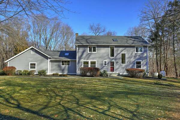 The gray colonial contemporary house at 104 Morehouse Road sits on a property of nearly one acre across the street from the 18-hole H. Smith Richardson Golf Course.