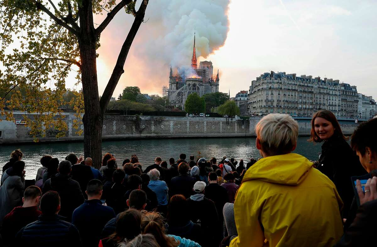 Bystanders look on as flames and smoke billow from the roof at Notre-Dame Cathedral in Paris on April 15, 2019. - A fire broke out at the landmark Notre-Dame Cathedral in central Paris, potentially involving renovation works being carried out at the site, the fire service said.Images posted on social media showed flames and huge clouds of smoke billowing above the roof of the gothic cathedral, the most visited historic monument in Europe. (Photo by GEOFFROY VAN DER HASSELT / AFP)GEOFFROY VAN DER HASSELT/AFP/Getty Images