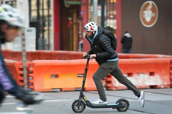 A commuter rides an e-scooter on Townsend Street in San Francisco, Calif. on Tuesday, March 19, 2019.