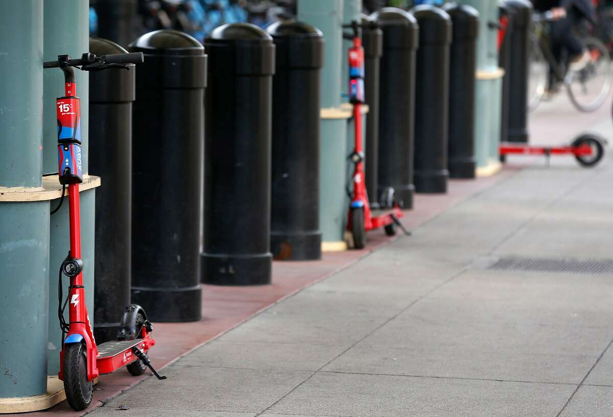 Scoot e-scooters are parked at the Caltrain station on Townsend Street in San Francisco, Calif. on Tuesday, March 19, 2019.