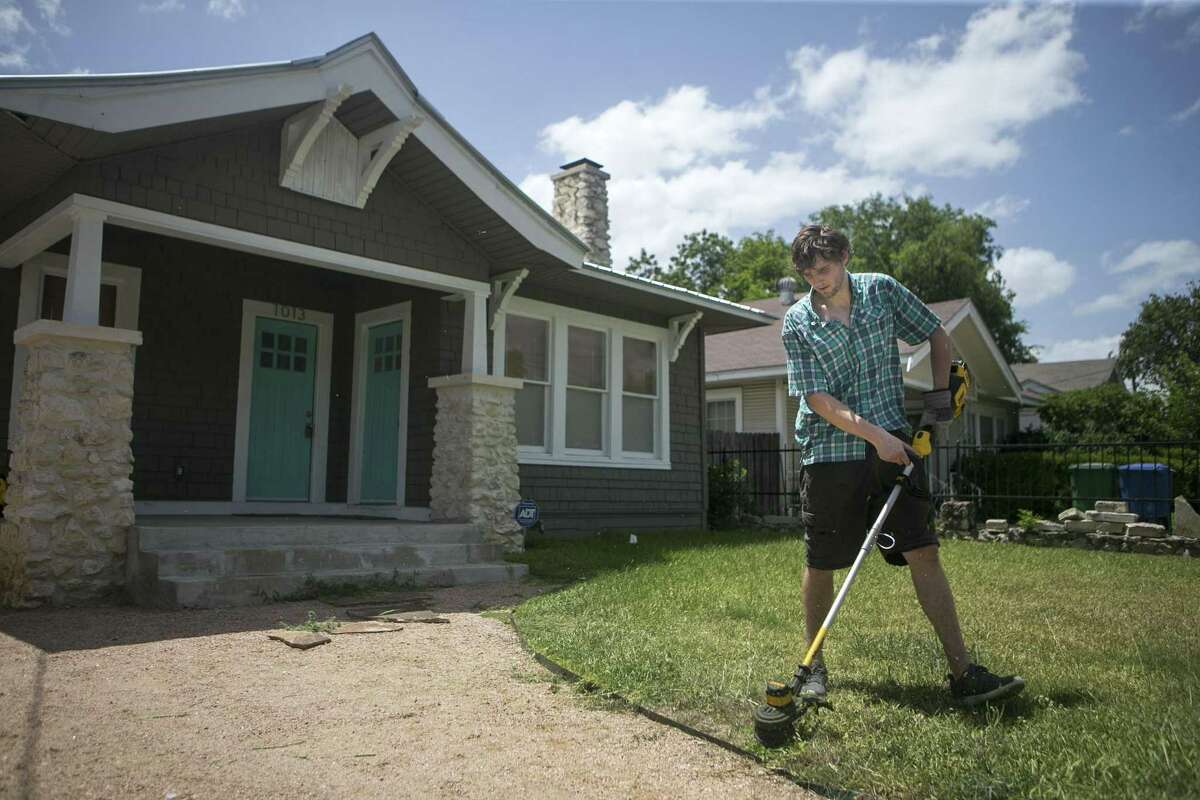 John Chism weed wacks the lawn of an Airbnb rental.