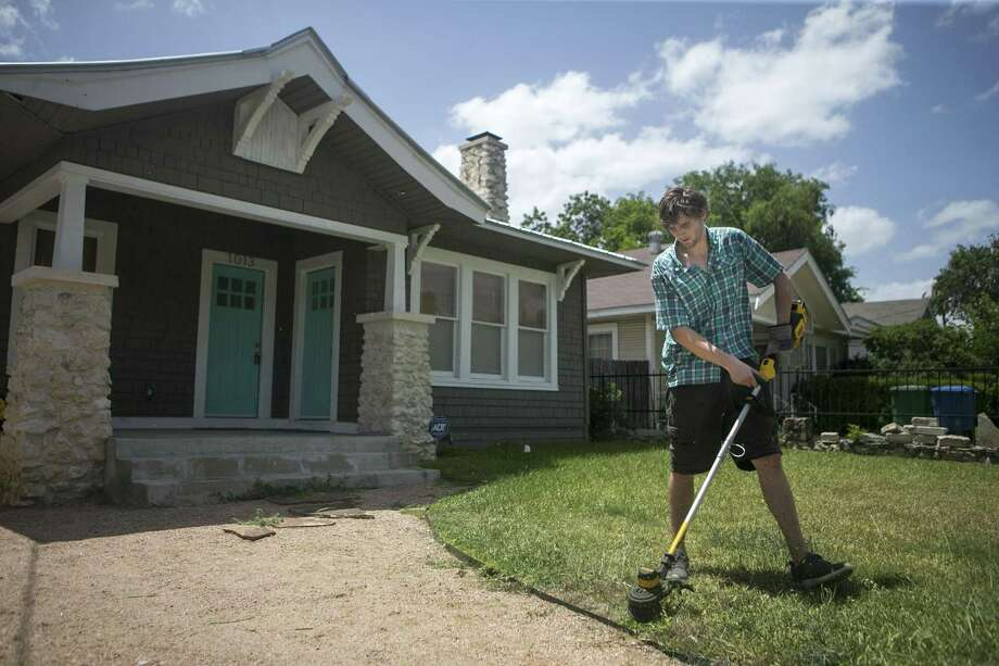 John Chism weed wacks the lawn of an Airbnb rental. Photo: Josie Norris, Staff / San Antonio Express-News / © San Antonio Express-News
