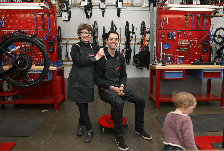 Owners Karen Wiener and Brett Thurber (with their daughter in foreground) of New Wheel at their new space for e-bike service and maintenance, which is close to their shop on Cortland Avenue in Bernal Heights. (The service center is not open to the public.) Photo: Liz Hafalia / The Chronicle