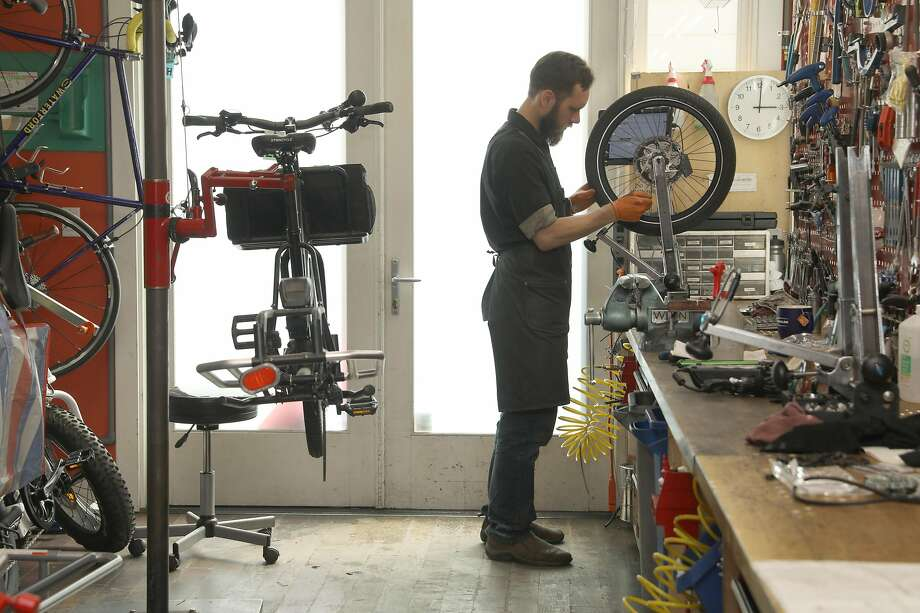 Jeremy Medina works on a tire at the New Wheel shop on Cortland Avenue in Bernal Heights. Photo: Liz Hafalia / The Chronicle