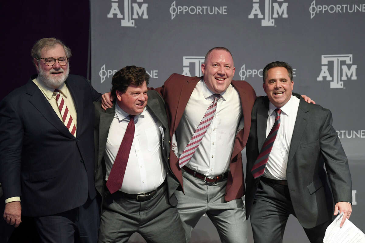 Texas A&M University System Board of Regents Chairman Charles Schwartz, left, joins athletic director Scott Woodward, new men's basketball coach Buzz Williams, second from right, and announcer Andrew Monaco in the Aggie War Hymn in College Station, Texas, Thursday, April 4, 2019. (Laura McKenzie/College Station Eagle via AP)