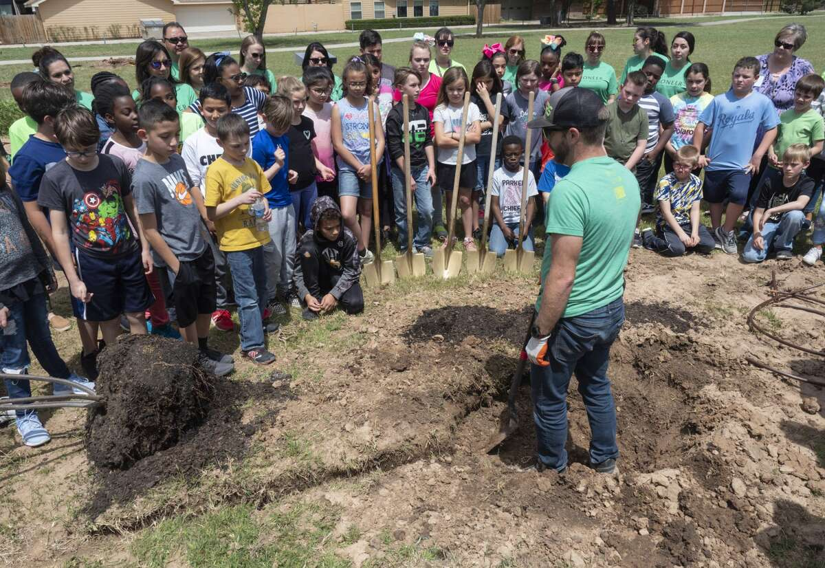 Marc Beaudoing, urban forester with Texas Trees Foundations, demonstrates how to plant a tree 04/15/19 as Parker Elementary fourth graders join forces with Pioneer Natural Resources volunteers, KMB and Texas Trees Foundation to plant 25 new trees in Trinity Park. Tim Fischer/Reporter-Telegram
