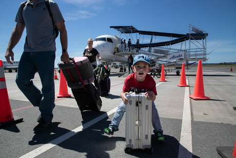 Simon Asselin, 5, rides a luggage alongside father Henry and mother Taryn (at left) after arriving at Charles M. Schulz�Sonoma County Airport on Friday, April 12, 2019, in Santa Rosa, Calif.