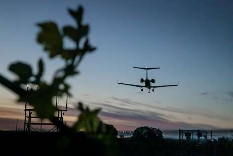 An airliner approaches Charles M. Schulz Sonoma County Airport above grape vines. Photo: Paul Kuroda / Special To The Chronicle