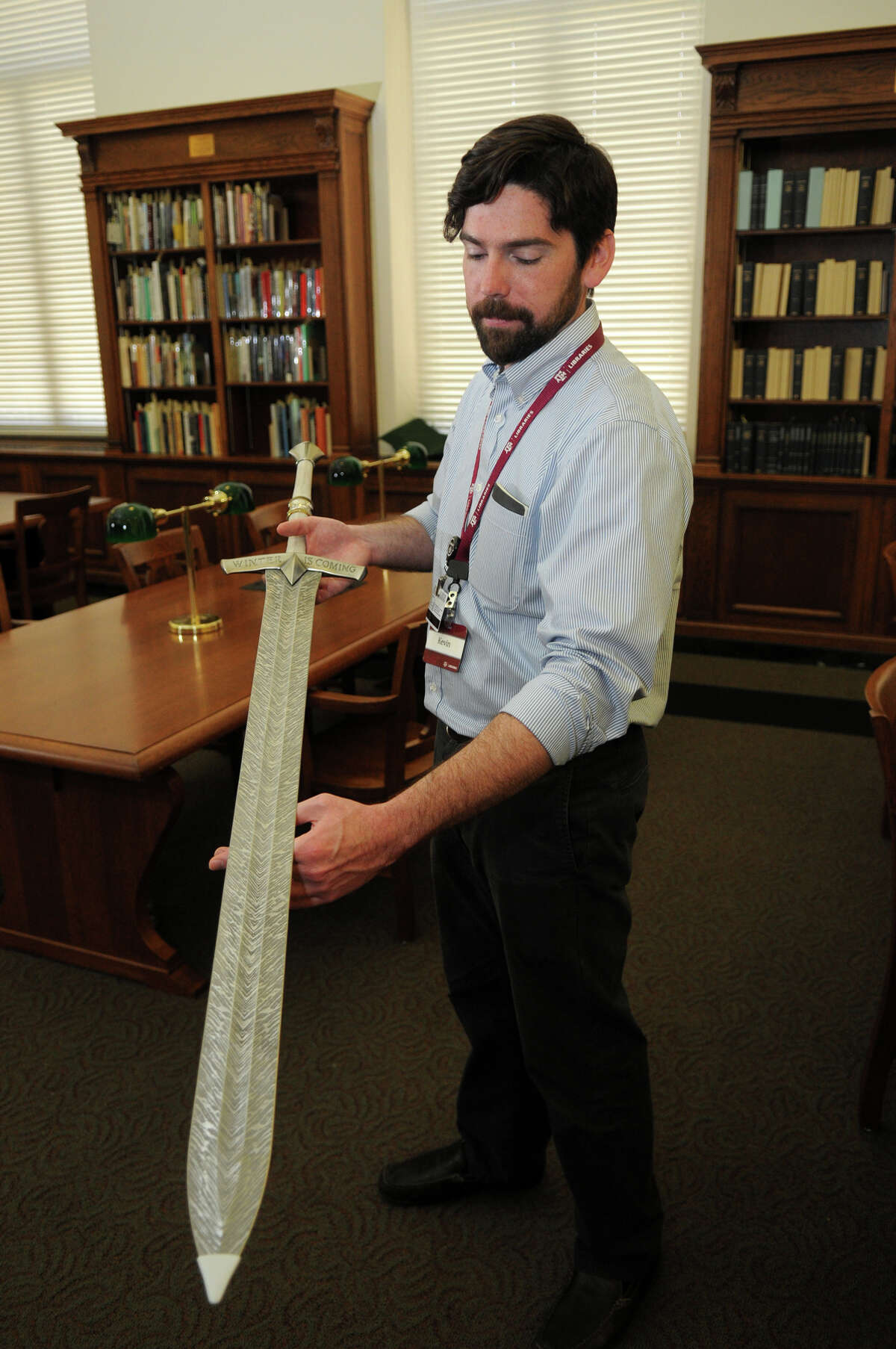 Kevin O'Sullivan, Instructional Assistant Professor and Outreach and Public Service Curator at the Cushing Memorial Library & Archives on the campus of Texas A&M University, shows off a replica of Ice, the ancestral greatsword of House Stark, carried by Ned until his arrest and used to execute him, produced by Valyrian Steel.