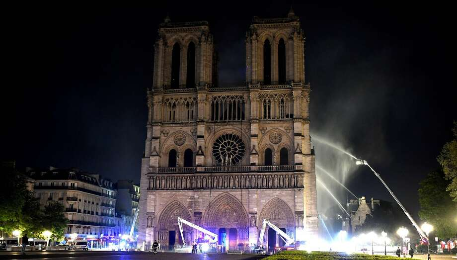 Fire fighter douse the Notre-Dame de Paris Cathedral after a fire broke out on April 15, 2019, in the French capital Paris. - A huge fire swept through the roof of the famed Notre-Dame Cathedral in central Paris on April 15, 2019, sending flames and huge clouds of grey smoke billowing into the sky. The flames and smoke plumed from the spire and roof of the gothic cathedral, visited by millions of people a year. A spokesman for the cathedral told AFP that the wooden structure supporting the roof was being gutted by the blaze. (Photo by STEPHANE DE SAKUTIN / AFP)STEPHANE DE SAKUTIN/AFP/Getty Images Photo: Stephane De Sakutin / AFP / Getty Images