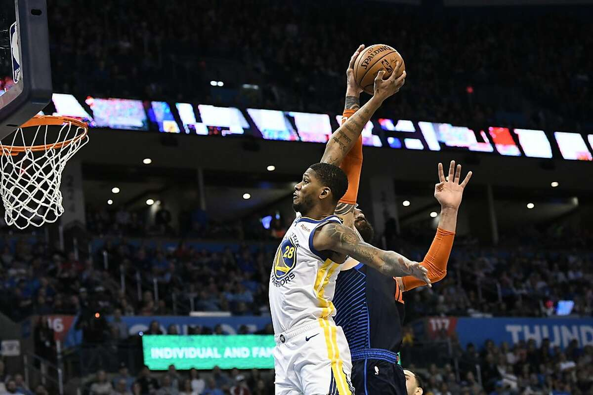 Oklahoma City Thunder center Steven Adams (12) blocks a shot by Golden State Warriors forward Alfonzo McKinnie (28) during the first half of an NBA basketball game Saturday, March 16, 2019, in Oklahoma City. (AP Photo/June Frantz Hunt)