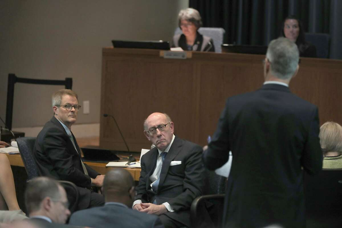 Former PG&E Board Chair Richard Kelly (left) and Kenneth Feinberg (middle), former director of executive compensation, Department of Treasury, listen to questions from the public as the California Public Utilities Commission hosts a daylong hearing about restructuring options for PG&E on Monday, April 15, 2019, in San Francisco, Calif.