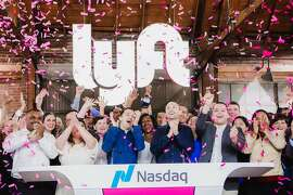 FILE -- Lyft co-founders John Zimmer, center left, and Logan Green, center right, at the company's IPO party in Los Angeles, March 29, 2019. With so many tech firms listing their shares this year, each is trying to avoid the traffic jam to get their own moment in the sun. (Alex Welsh/The New York Times)