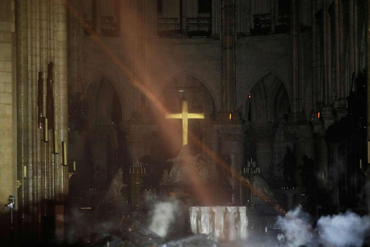 Smoke rises around the alter in front of the cross inside the Notre-Dame Cathedral as the fire continues to burn on April 16, 2019 in the French capital Paris. - A huge fire swept through the roof of the famed Notre-Dame Cathedral in central Paris on April 15, 2019, sending flames and huge clouds of grey smoke billowing into the sky. The flames and smoke plumed from the spire and roof of the gothic cathedral, visited by millions of people a year. A spokesman for the cathedral told AFP that the wooden structure supporting the roof was being gutted by the blaze. (Photo by PHILIPPE WOJAZER / POOL / AFP)PHILIPPE WOJAZER/AFP/Getty Images