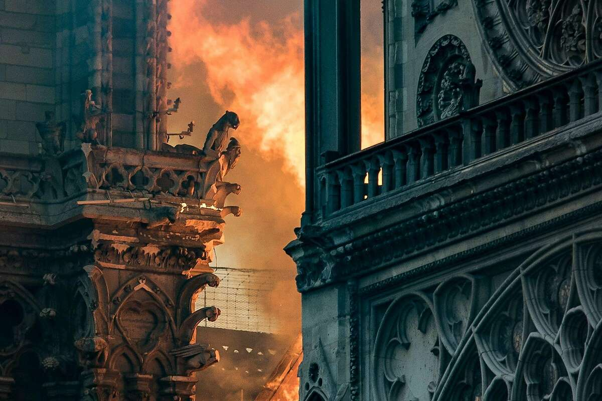 Flames and smoke billow around the gargoyles decorating the roof and sides of the Notre-Dame Cathedral in Paris on April 15, 2019. - A huge fire swept through the roof of the famed Notre-Dame Cathedral in central Paris on April 15, 2019, sending flames and huge clouds of grey smoke billowing into the sky. The flames and smoke plumed from the spire and roof of the gothic cathedral, visited by millions of people a year. A spokesman for the cathedral told AFP that the wooden structure supporting the roof was being gutted by the blaze. (Photo by THOMAS SAMSON / AFP)THOMAS SAMSON/AFP/Getty Images