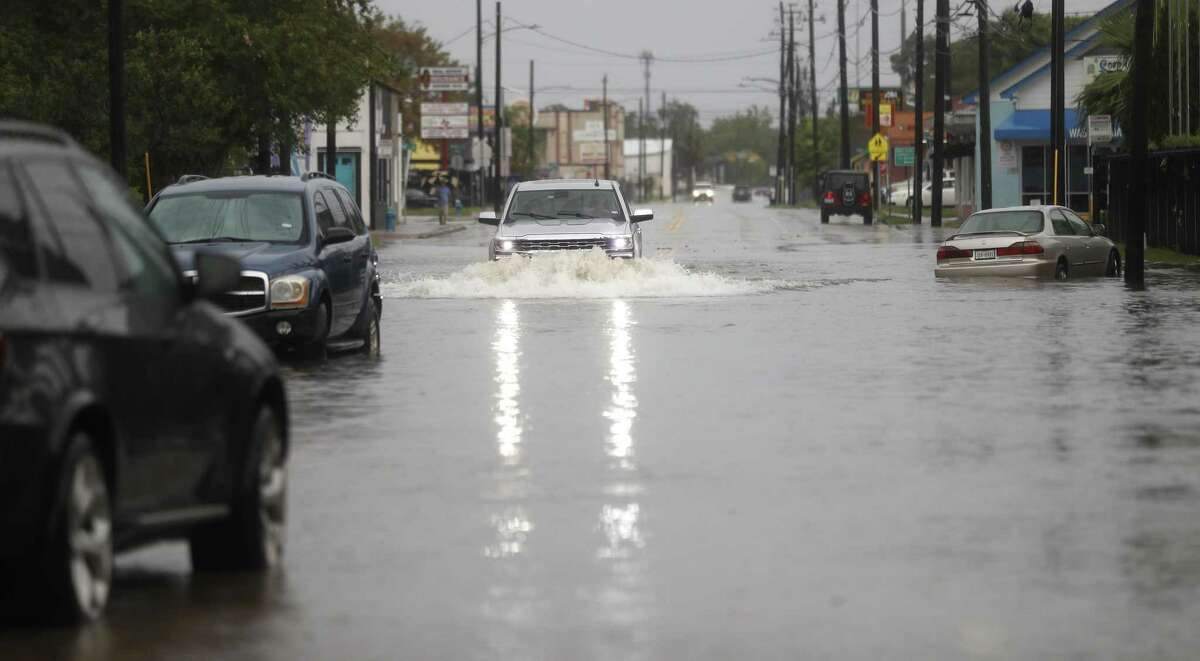 A truck drives through flood water near flooded out cars on North Main Street in the Heights, after heavy rain from Hurricane Harvey fell overnight, Sunday, Aug. 27, 2017, in Houston. ( Karen Warren / Houston Chronicle )