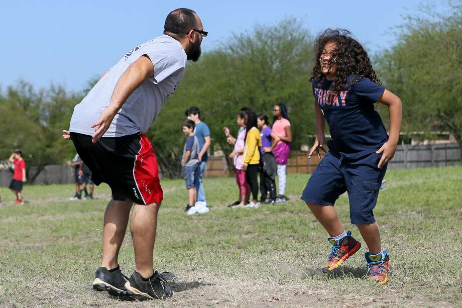 Miguel Babilolia, right, and volunteer Nicholas Guerrero work on some football conditioning drills at Copperfield Elementary as part of the Fuel Up to Play 60, a national program that teaches kids about the importance of healthy diets and regular activity for 60 minutes every day. Photo: Marvin Pfeiffer / Staff Photo / Express-News 2019