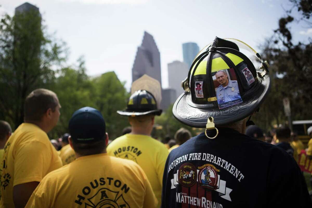 """A Houston firefighter wears a helmet on Tuesday, March 19, 2019, in Houston with the photo of Captain William Ross """"Iron Bill"""" Dowling, a firefighter who was seriously injured in the 2013 motel fire and about four years after the injuries he died."""
