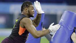 Michigan defensive lineman Rashan Gary runs a drill during the NFL football scouting combine, Sunday, March 3, 2019, in Indianapolis.