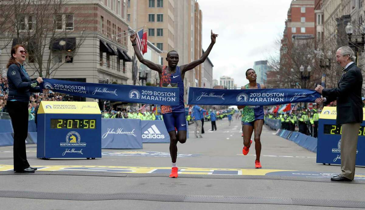 Lawrence Cherono, of Kenya, breaks the tape to win the 123rd Boston Marathon in front of Lelisa Desisa, of Ethiopia, right, on Monday, April 15, 2019, in Boston. (AP Photo/Winslow Townson)