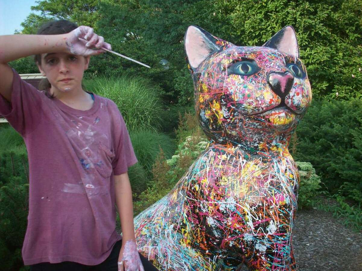 """Isabel Lane, 11, wore a paint-smeared shirt and posed with a paintbrush, fto pose with artist Nina Bentley's ìCatson Pollock,"""""""