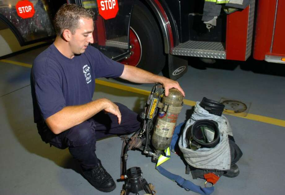 Fairfield firefighter Dennis Eannotti demonstrates how he inspects his self contained breathing apparatus, which includes a bottle of compressed. Photo: Ned Gerard / Connecticut Post