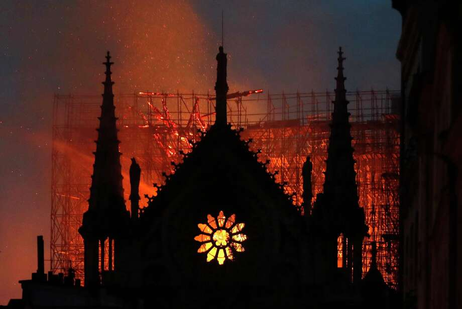 Flames and smoke rise from Notre Dame cathedral as it burns in Paris, Monday, April 15, 2019. Massive plumes of yellow brown smoke is filling the air above Notre Dame Cathedral and ash is falling on tourists and others around the island that marks the center of Paris. (AP Photo/Thibault Camus) Photo: Thibault Camus / Copyright 2019 The Associated Press. All rights reserved.