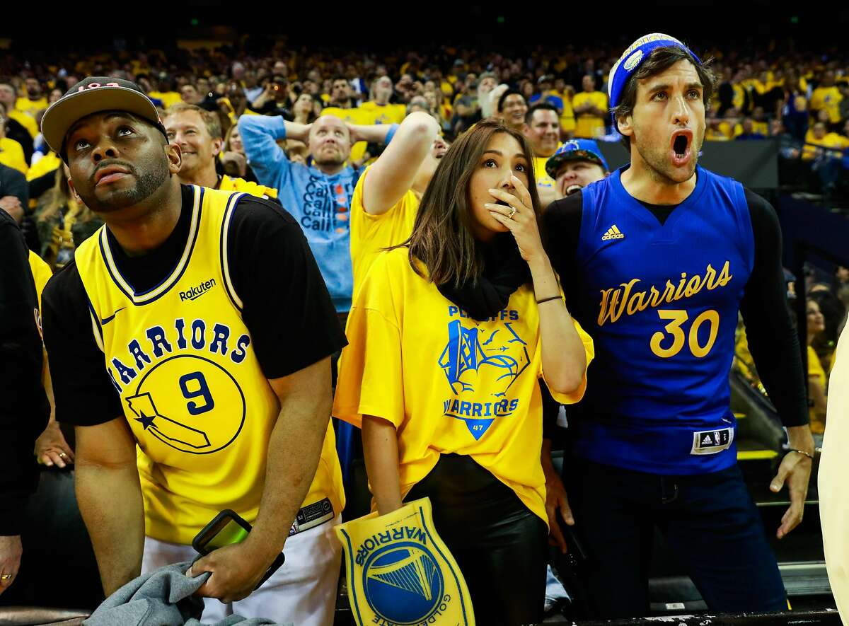 (l-r) Jerald Dodson, Solenn Heussaff and Nico Balzico gasp during the fourth quarter of Game 2 of the Western Conference Playoffs between the Golden State Warriors and the Los Angeles Clippers at Oracle Arena in Oakland, California, on Monday, April 15, 2019.