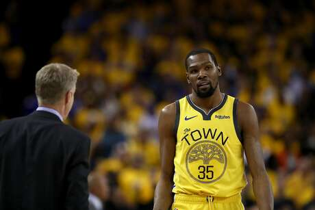 OAKLAND, CALIFORNIA - APRIL 15:  Kevin Durant #35 of the Golden State Warriors talks to head coach Steve Kerr during Game Two of the first round of the 2019 NBA Western Conference Playoffs at ORACLE Arena on April 15, 2019 in Oakland, California.  NOTE TO USER: User expressly acknowledges and agrees that, by downloading and or using this photograph, User is consenting to the terms and conditions of the Getty Images License Agreement.  (Photo by Ezra Shaw/Getty Images)