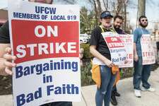 Union members of Stop & Shop hold signs while on strike against the company over stalled contract talks.