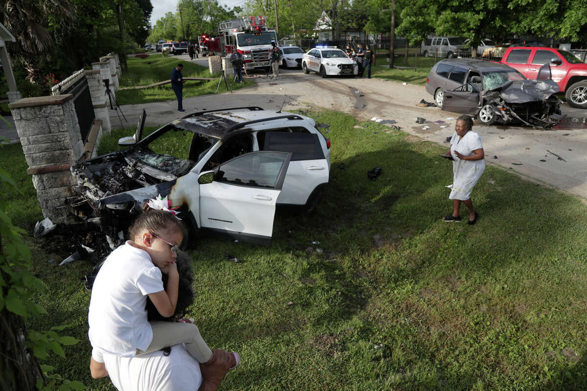 People stand nearby as authorities investigate the scene of a two-vehicle crash in the 11800 block of Vickery Tuesday, April 16, 2019, in Houston.