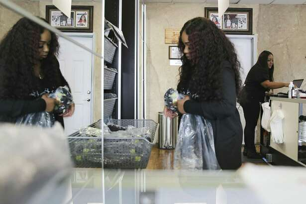 She's Happy Hair employees Jazmynn McGee, left, and Meaghan Reeves work at the company's first storefront on Friday, March 1, 2019. Entrepreneur Warren Broadnax, one of the owners of She's Happy Hair, started the business in 2012.