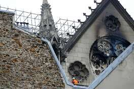 A man is pictured near chared glass windows Notre Dame cathedral Tuesday April 16, 2019 in Paris. Firefighters declared success Tuesday in a more than 12-hour battle to extinguish an inferno engulfing Paris' iconic Notre Dame cathedral that claimed its spire and roof, but spared its bell towers. (AP Photo/Francois Mori)