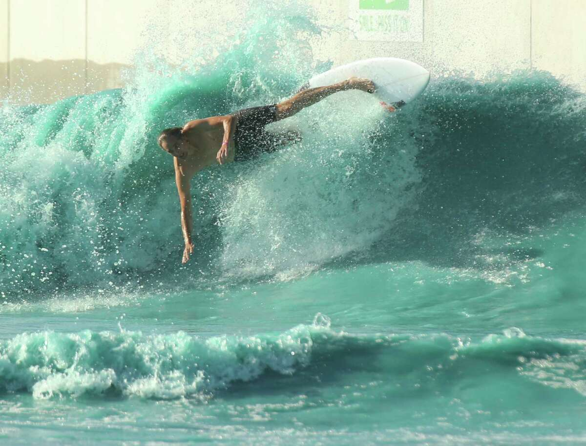In this Saturday, July 14, photo, a surfer takes a spill while battling the waves at the BSR Surf resort near Waco, Texas. >> Keep clicking through this gallery to see the history of Houston-area waterparks.