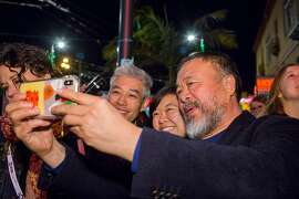 Ai Weiwei poses with fans for selfies